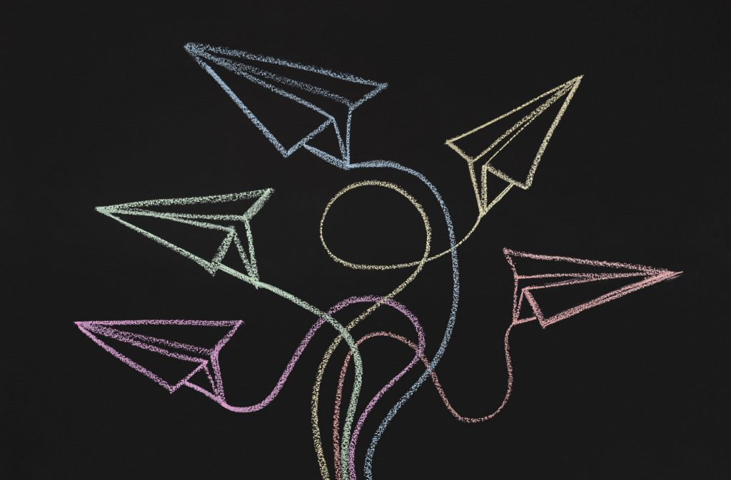 Drawn paper planes with route trace on chalkboard background