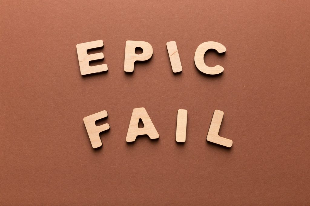 Wooden letters spelling Epic fail on brown background
