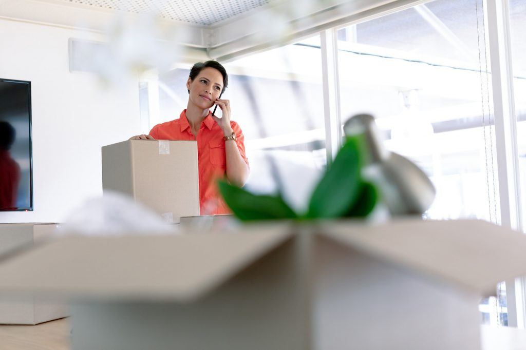 Front view of beautiful businesswoman with cardboard boxes talking on mobile phone in new office